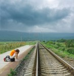 woman waiting for train by tracks
